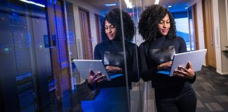 Woman uses Microsoft Surface Laptop Near Data Center Servers Floor Office IT Building Standing Black Clothes RegTech Explainer Article Legal Tech FinTech