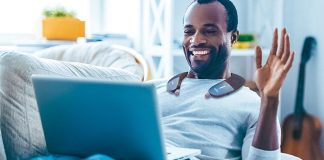 BeHear Proxy Review Man Using Neck Speaker For Video Conference on Laptop Smiling