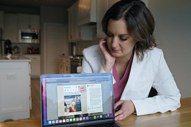 A woman in a white lab coat sitting in a kitchen points a laptop screen to the viewer