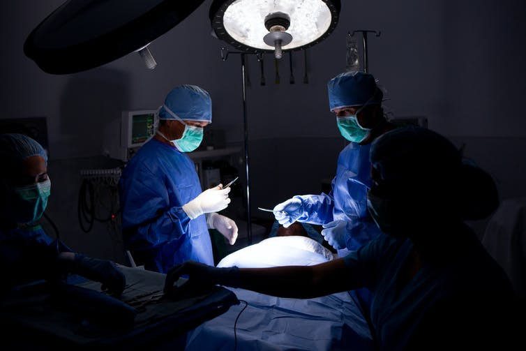 preparing for operation in darkened surgical suite