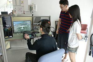 English: Students working on a flight simulati...