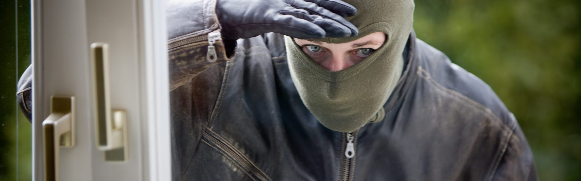 Cambrioleur qui inspecte l'intérieur d'une maison avec un pied de biche et une lampe torche