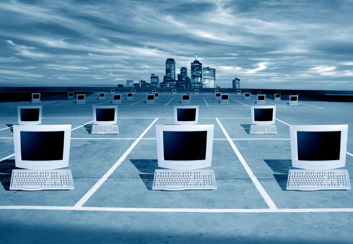 PCs on a grid in front of a city skyline.