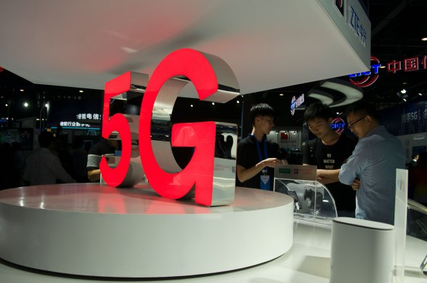 Attendees look at 5G mobile phones at the Qualcomm stand during China Mobile Global Partner Conference 2018 at Poly World Trade Center Exhibition Hall on December 6, 2018 in Guangzhou, Guangdong Province of China.