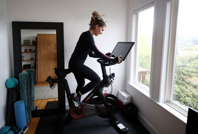 SAN ANSELMO, CALIFORNIA - APRIL 06: Cari Gundee rides her Peloton exercise bike at her home on April 06, 2020 in San Anselmo, California. More people are turning to Peloton due to shelter-in-place orders because of the coronavirus (COVID-19). Peloton stock has continued to rise over recent weeks even as most of the stock market has plummeted. However, Peloton announced today that they will temporarily pause all live classes until the end of April because an employee tested positive for COVID-19. (Photo by Ezra Shaw/Getty Images)