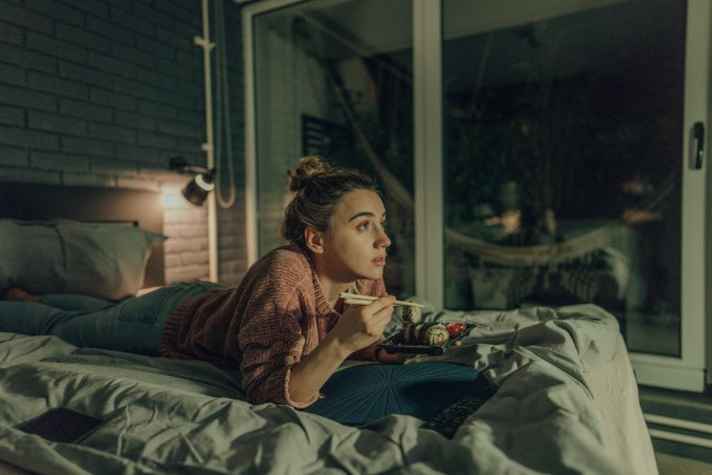 Photo of a young woman watching TV in the bedroom of her apartment; eating sushi and enjoying her night at home alone.