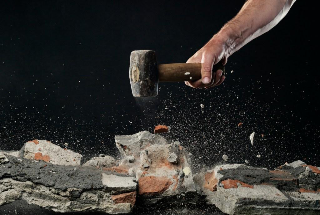 Smashing brick work with hammer