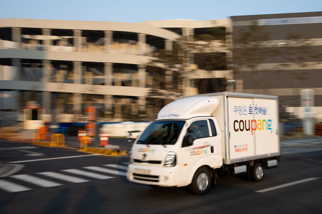 A Coupang Corp. delivery truck drives past a company's fulfillment center in Bucheon, South Korea, on Friday, Feb. 19, 2021. South Korean e-commerce giant Coupang filed for an initial public offering in the U.S. and that could raise billions of dollars to battle rivals and kick off a record year for IPOs in the Asian country. Photographer: SeongJoon Cho/Bloomberg via Getty Images