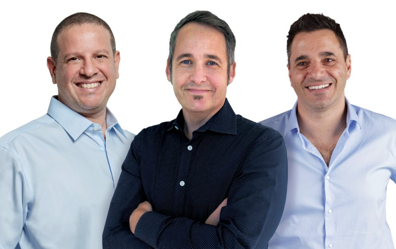 A group photo of Trax's co-founders, Joel Bar-El (left) and Dror Feldheim (right), and Trax's CEO, Justin Behar (center)