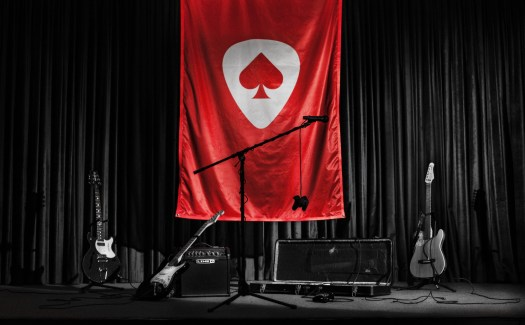The Game Band logo on a flag behind several instruments.