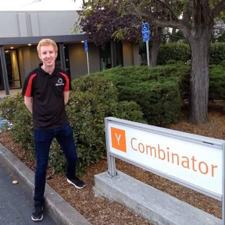 Alba Orbital founder Tom Walkinshaw next to a Y Combinator sign.