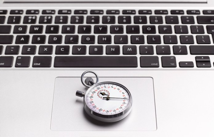 Close up of a stopwatch on a laptop's trackpad.