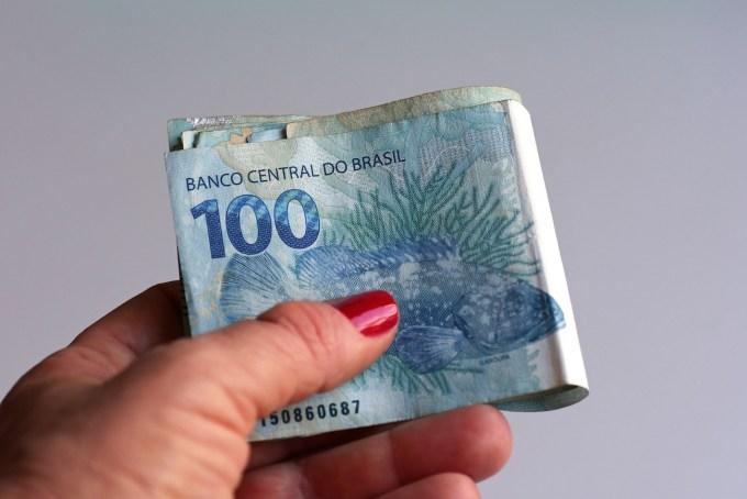 Mano femenina sosteniendo dinero brasileño (Real / Reais)