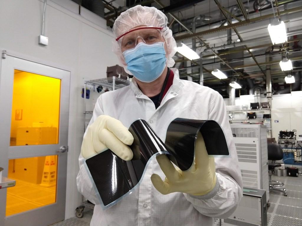 "A lab technician shows the flexibility of a Regher ""solar blanket."""
