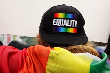 "Person wearing hat saying ""equality"" and with rainbow flag"