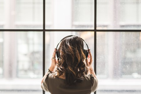 Girl with black headphones looking out window