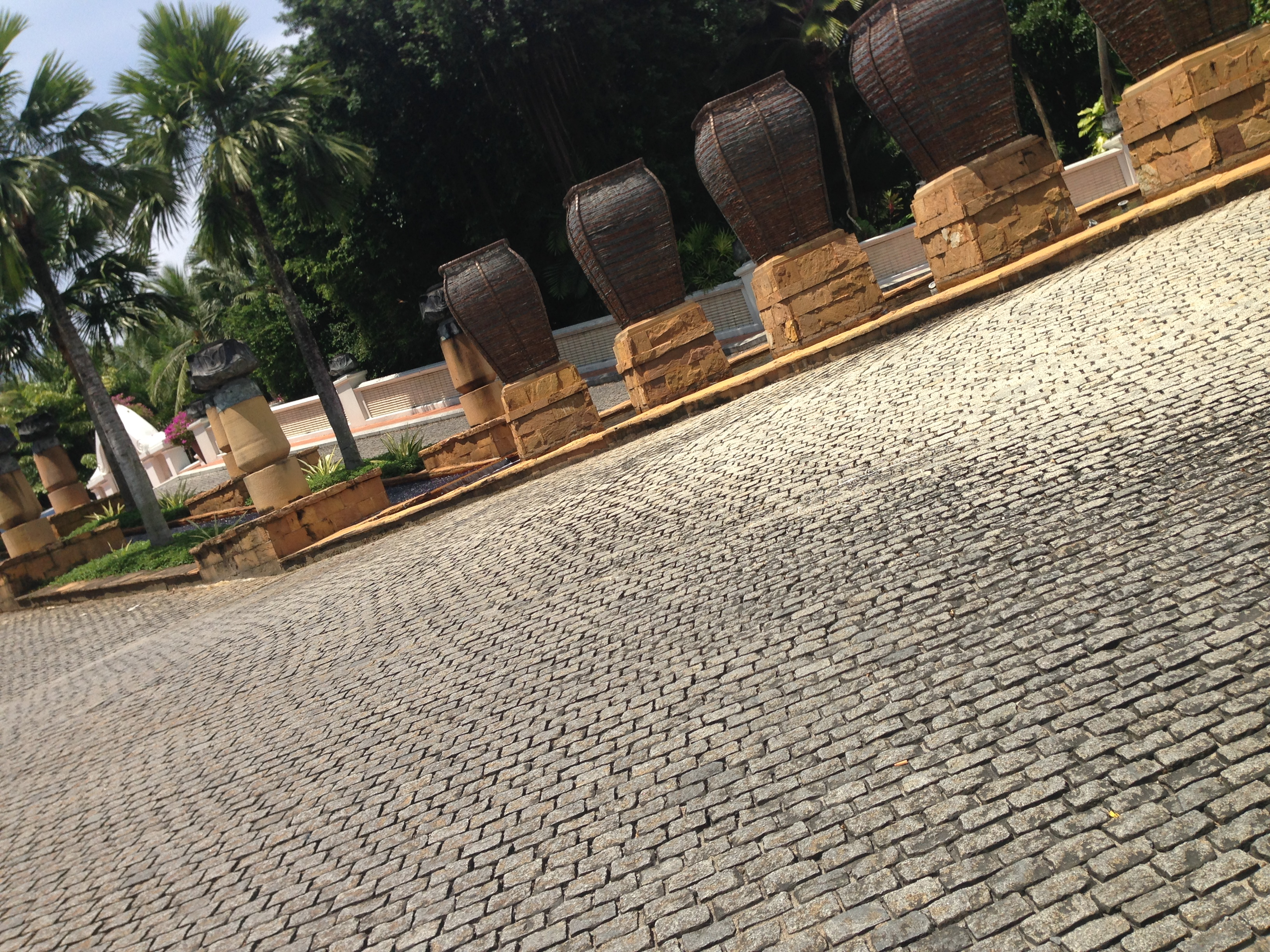 Photo of the drive way leading up to the JW Marriott reception. The drive-way is cobbled. You can see a clump of palms in the distance, and on your right you can see stone coloured urns, which are lit up at night.