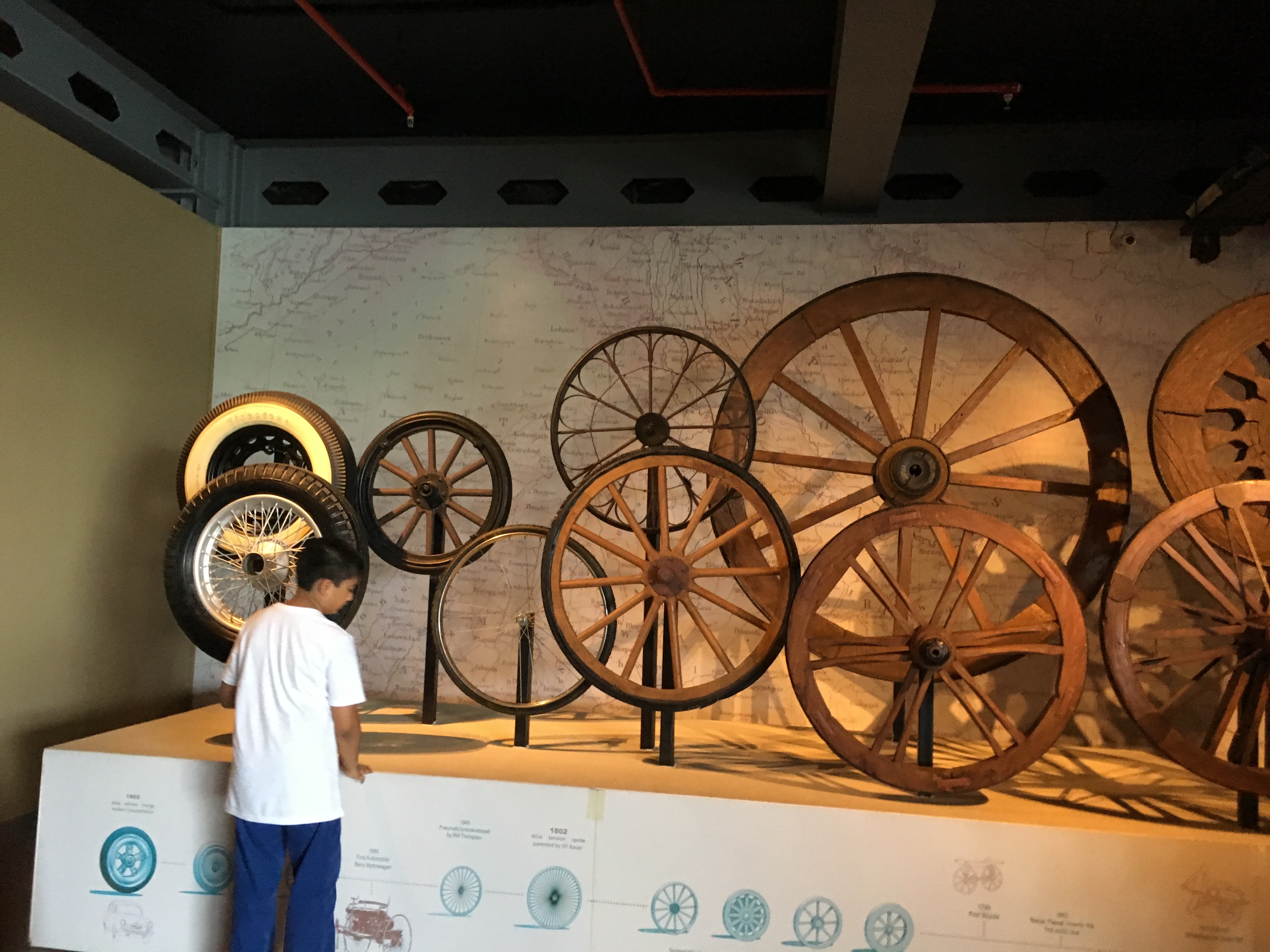 Depicts evolution of wheels through ages