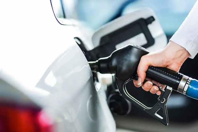 Woman pumping petrol at gas station into vehicle.