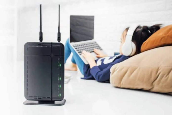 Wireless router and kids using a laptop in home Casezy idea / Shutterstock.com