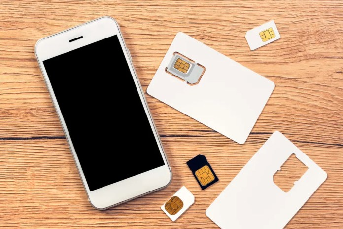Smartphone with blank screen and SIM cards on the table,