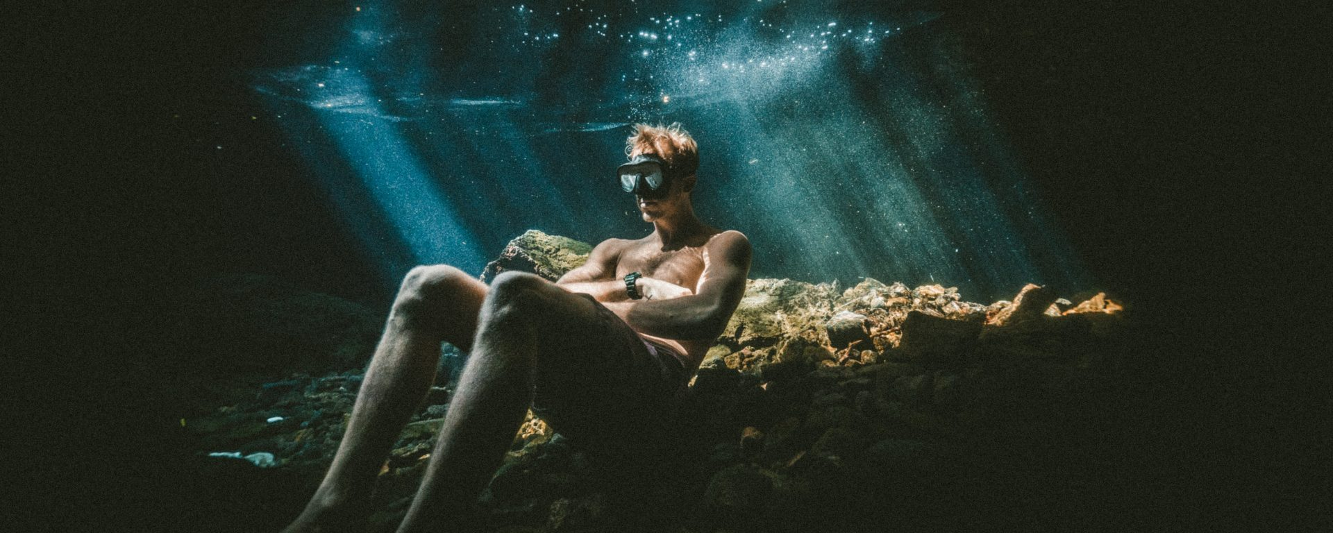 a man sitting underwater - an effect that could be achieved with adobe photoshop elements