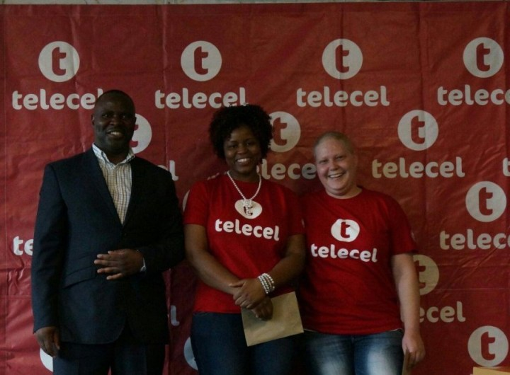 Mr Godzi pictured with Faith Musevenzi and Chianne Godwin, both from Telecel's Sales Department, after handing to them the proceeds of Telecel's fund raising activities.