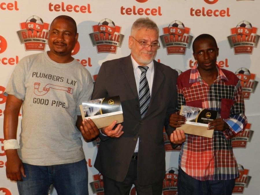 Mr De Jesus presenting Mr Chakasikwa (left) and Mr Dumisani with their World Cup tickets