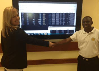 The MD of STT Michelle Janke and the CEO of the DSE Moremi Marwa shake hands as the system goes live for the first time at the Tanzanian Exchange