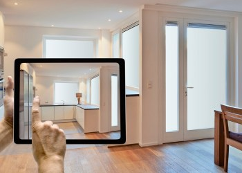 Mobile device with man hands taking picture in modern kitchen renovated
