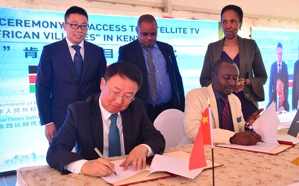 hinese Ambassador to Kenya Mr. Wu Peng (seated left) and Hesbon Malweyi ICT Director (seated right) sign the technical document transfer during the handover of the 10,000 digital television project