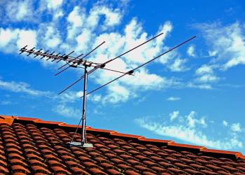 TV antenna on a rooftop with blue sky and white clouds background