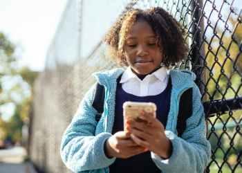 content black girl using smartphone in autumn park