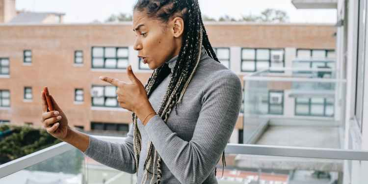 mad ethnic female gesticulating while having video conversation on smartphone on terrace