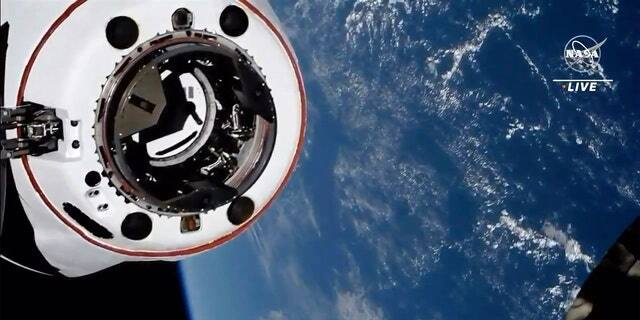 This image made from NASA TV shows the SpaceX Crew Dragon spacecraft, with the Earth behind, approaching the international space station, Saturday, April 24, 2021. The recycled SpaceX capsule carrying four astronauts has arrived at the International Space Station, a day after launching from Florida. (NASA via AP)