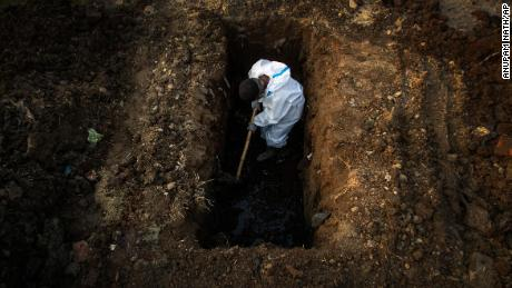 A man in protective suit digs earth to bury the body of a Covid-19 victim in Gauhati, India, on April 25.