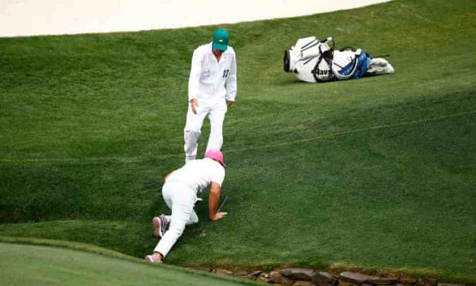 Brooks Koepka is helped out of the creek up by his caddie, Ricky Elliott, on the 13th hole.