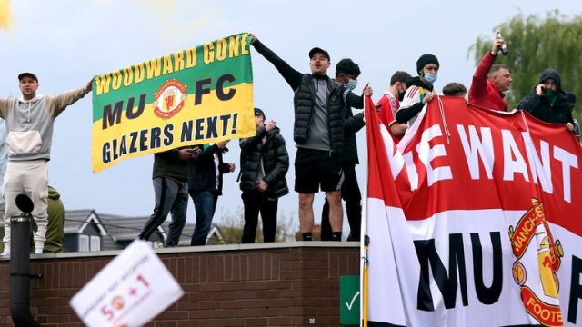 Fans holds up banners as they protest against the Glazer family, owners of Manchester United, before their Premier League match against Liverpool at Old Trafford