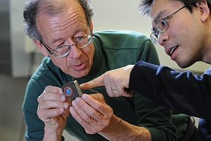 Arto Nurmikko, left, and co-author Ming Yin hold the wireless implant device (Fred Field, Brown University)