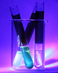The vials on the left contain quantum dots made with cadmium selenide in a solution; the vial on the right contains the solvent without quantum dots.