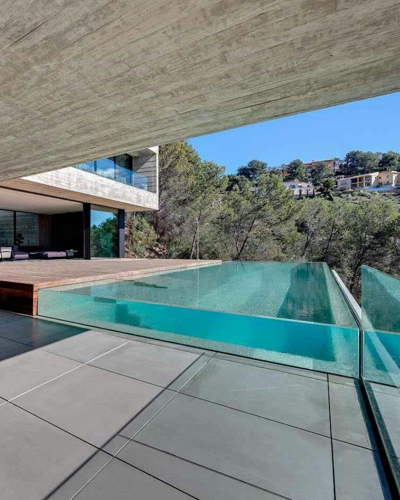 a glass ended swimming pool outside a luxury house
