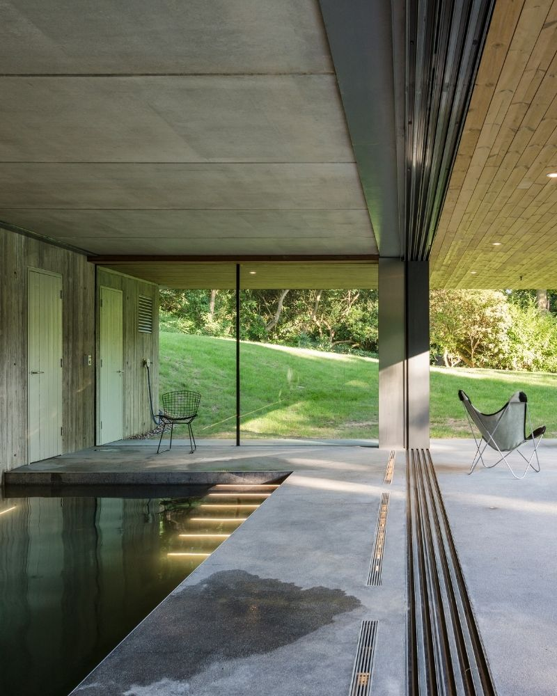 an indoor swimming pool with flush threshold sliding doors shown open