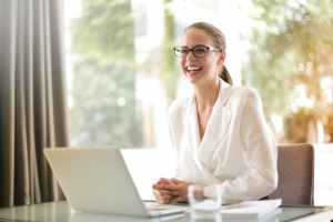 Artificial intelligence  and laughing businesswoman working in office with laptop