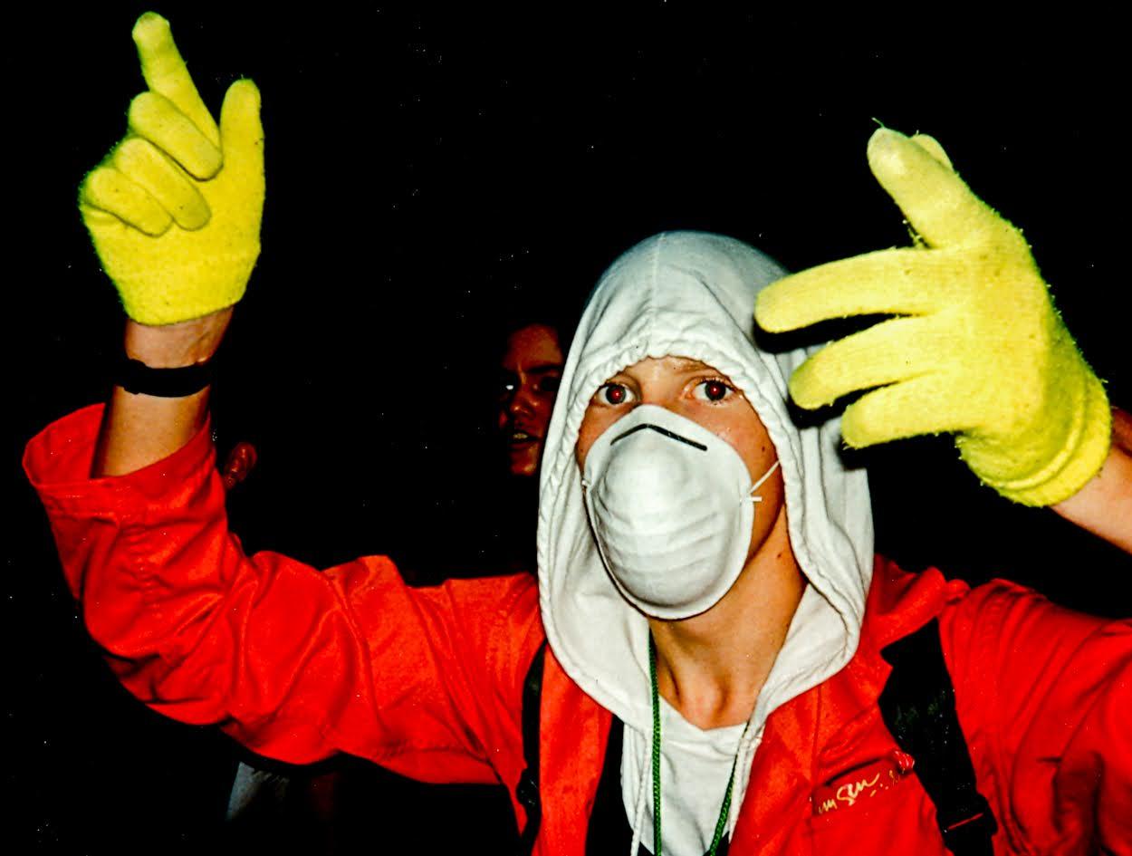 90er Raver im Maskenoutfit und Handschuehen