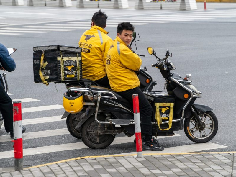 A Meituan-Dianping deliveryman waits for traffic on the streets of Shanghai on March 22, 2019.