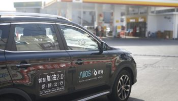 In this image from Alibaba, a car equipped with Alibaba's vehicle operating system AliOS is parked outside a gas station in Beijing in February 2018. (Image credit: Alibaba)