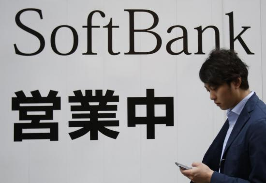 A man holding his mobile phone walks past the logo of Softbank Corp at its branch in Tokyo