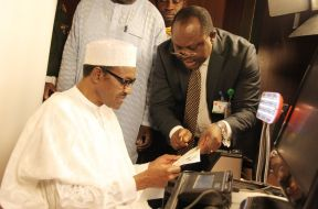 Chris Onyemenam, the Director-General of National Identity Management Commission (NIMC), on the right speaks with President Muhammadu Buhari, during the data capture of the President in Abuja
