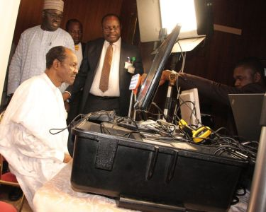 President Muhammadu Buhari, seated, undergoing the biometric capture by officials of the National Identity Management Commission (NIMC) in Abuja