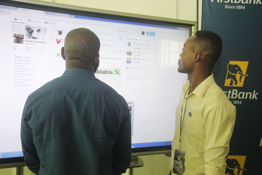 A man tries his luck to win a gift pack at the First Bank stand at Social Media Media Week Lagos
